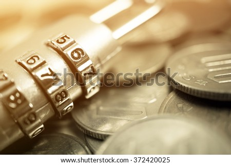 combination padlock on coin money for financial security concept