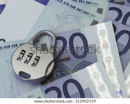 Combination padlock rests on Twenty Euro banknotes - stock photo