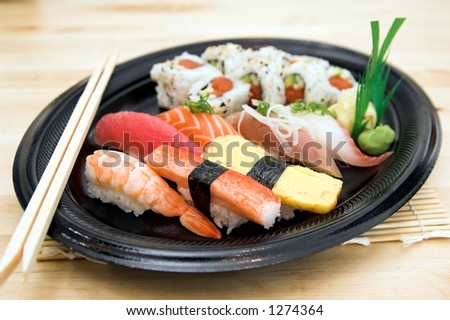Combination sushi plate with a spicy California sushi roll and salmon,tuna,whitefish,yellowtail,sweet egg, sweet shrimp and crab sushi garnished with wasabi and pickled ginger - stock photo