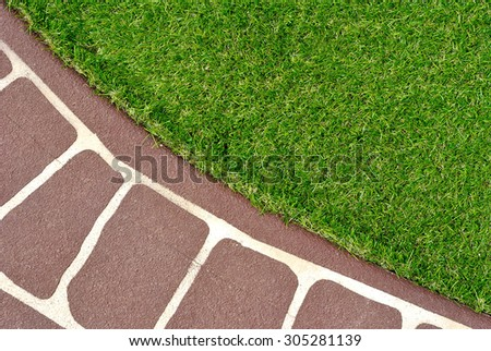 Combinations of stenciled concrete floor and green artificial grass - stock photo
