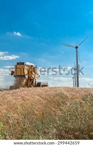 combine harvest in wheat field with wind turbine - stock photo
