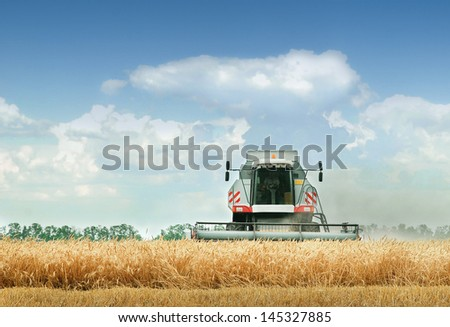 Combine harvester at work harvesting a field of crops - stock photo