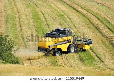 Combine harvester harvesting wheat cereal in farm - stock photo