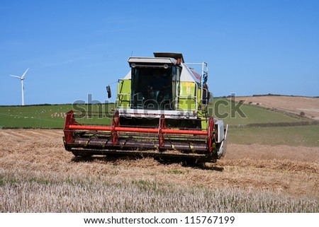Combine harvester in a field below wind turbines Isle of Anglesey - stock photo