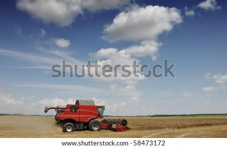 Combine harvester on blue sky - stock photo