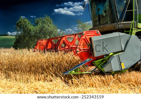 Combine harvester working at wheat field - stock photo