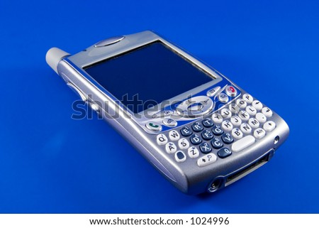 Combined cell phone and Personal Digital Assistant (PDA). Blue background. Focus is on the buttons in the lower left foreground. - stock photo