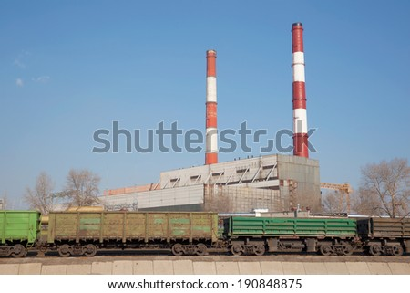 Combined heat and power plant with railway cargo cars in front - stock photo