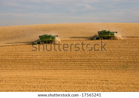 Combines harvesting wheat on a steep hillside in Idaho - stock photo