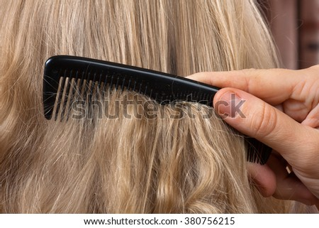 combing long blonde female hair - close up