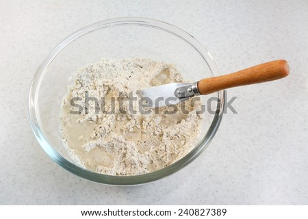 Combining water and bread flour mix with a flat-bladed palette knife - stock photo