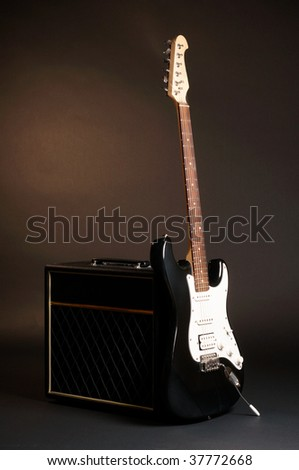 Combo and guitar on black background - stock photo
