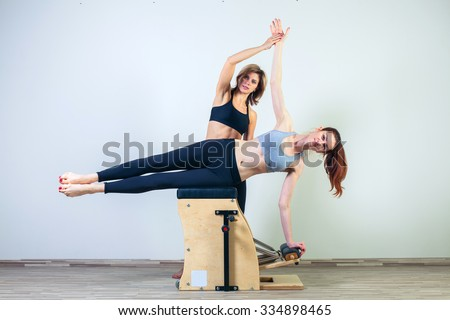 combo wunda pilates chair woman with instructor fitness yoga gym exercise. - stock photo