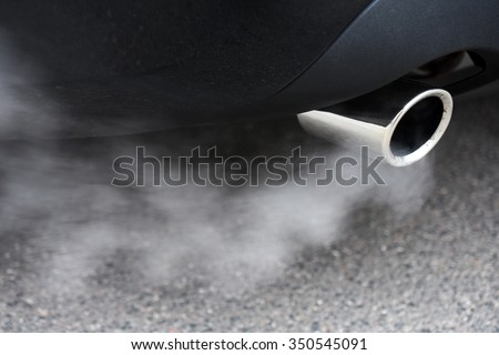 Combustion fumes coming out of car exhaust pipe - stock photo