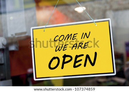 come in we are open sign hanging on a window door outside a restaurant, store, office or other - stock photo