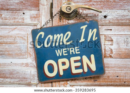 Come In We're Open on the wooden door, copyspace on the right. - stock photo