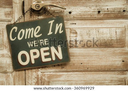 Come In We're Open on the wooden door, copyspace on the right. vintage retro style - stock photo