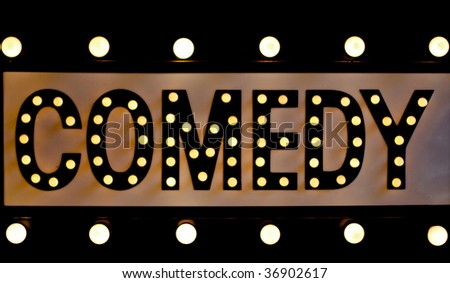 comedy sign lit up in lights on a retro sign - stock photo