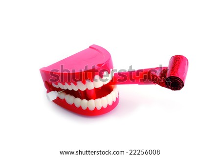 Comedy wind-up chattering teeth biting party blower isolated on white with clipping path - stock photo