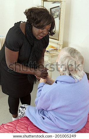 comfort and support from  care giver to elderly woman at home - stock photo