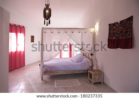 comfortable and cozy white and red guess bedroom  - stock photo