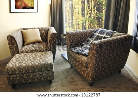 Comfortable armchairs with cushion and ottoman. Photo on the wall is my own. - stock photo