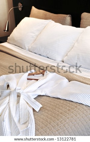 Comfortable bed with clean bathrobe in upscale hotel