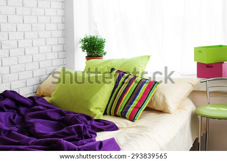 Comfortable bed with colorful pillows and purple blanket in bedroom - stock photo