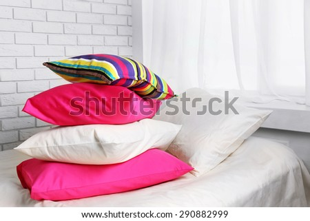 Comfortable bed with colorful pillows in bedroom - stock photo
