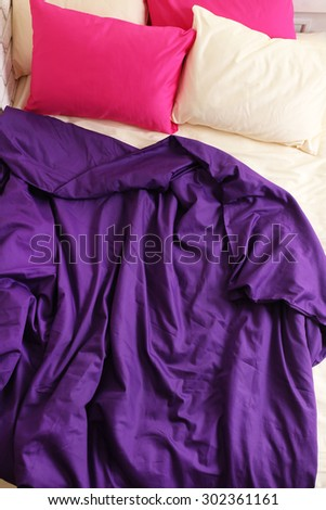 Comfortable bed with pink pillows and purple blanket in bedroom - stock photo