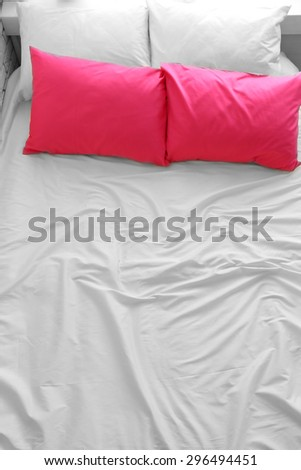 Comfortable bed with pink pillows in bedroom - stock photo