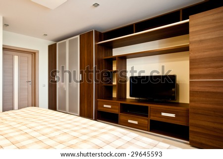 Comfortable bedroom with TV and wardrobes - stock photo
