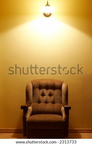 Comfortable brown armchair standing below wall lamp - stock photo
