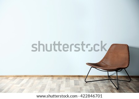 Comfortable chair on blue wall background - stock photo