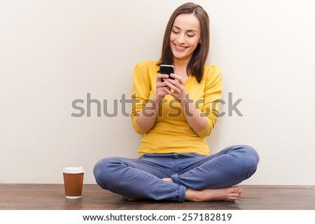 Comfortable communication. Picture of beautiful young woman holding mobile phone while sitting on the floor against brown background - stock photo