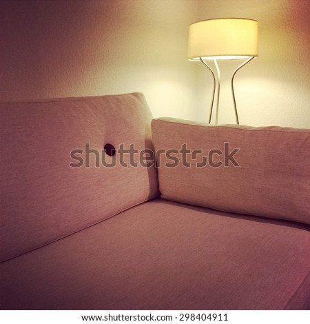 Comfortable fabric sofa and cozy lamp in the living room. - stock photo