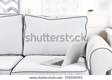Comfortable grey sofa with notebook on it in living room, close up - stock photo