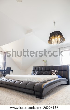 Comfortable king size bed in modern bedroom - stock photo