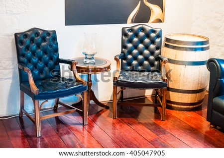 comfortable leather chairs next to a barrel