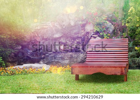 Comfortable lounge chair in a small garden - stock photo