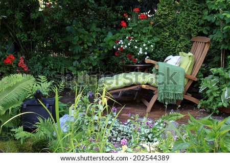 Comfortable lounge chair in a small garden. Also available in vertical. - stock photo