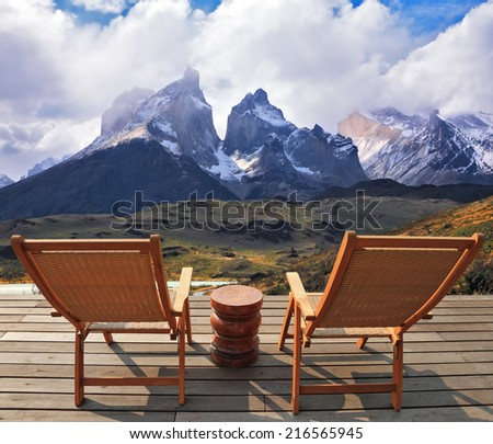 Comfortable lounge chairs on wooden platform for rest and observation. Gorgeous snow-covered rocks in the national park Torres del Paine - stock photo