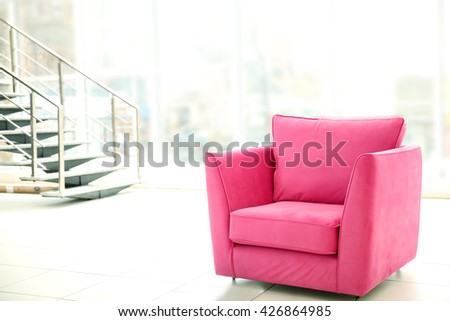Comfortable pink chair indoors - stock photo