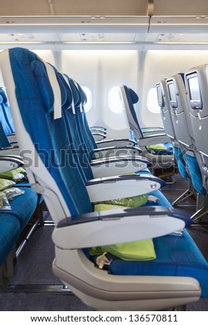 Comfortable seats in aircraft cabin with screens in chairs back - stock photo