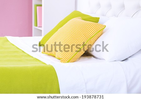 Comfortable soft bed with pillows in room - stock photo
