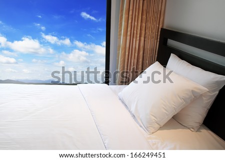 Comfortable soft pillows on the bed  with blue sky - stock photo
