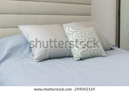 Comfortable soft pillows on the light blue bed - stock photo