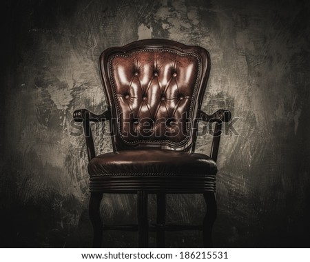Comfortable wooden chair against concrete wall - stock photo