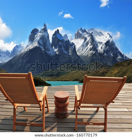 Comfortable wooden chair - chaise lounges stand on a wooden platform. Lookout is arranged in front of the famous cliffs of Los Kuernos. National Park Torres del Paine, Patagonia, Chile. Collage - stock photo