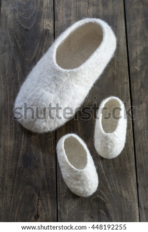 Comfortable wool home shoes on wooden background - stock photo
